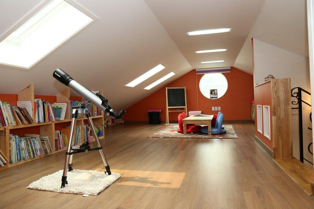 attic room with bookcase and telescope