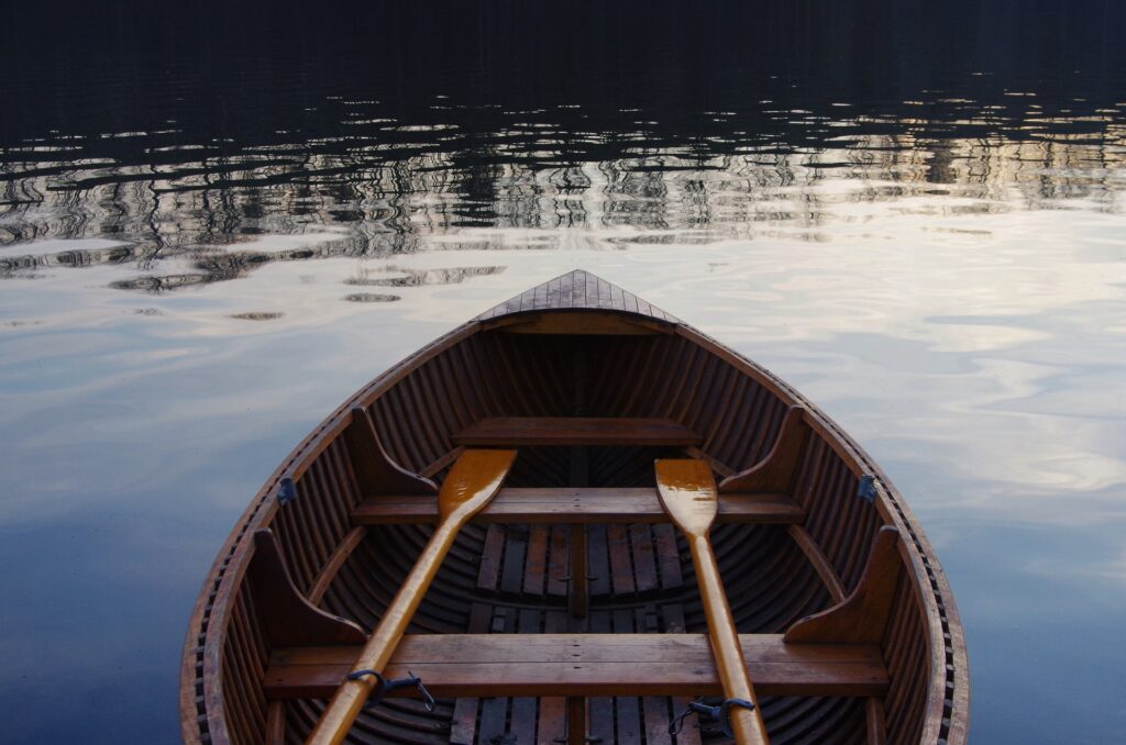 rowboat with oars floating on water