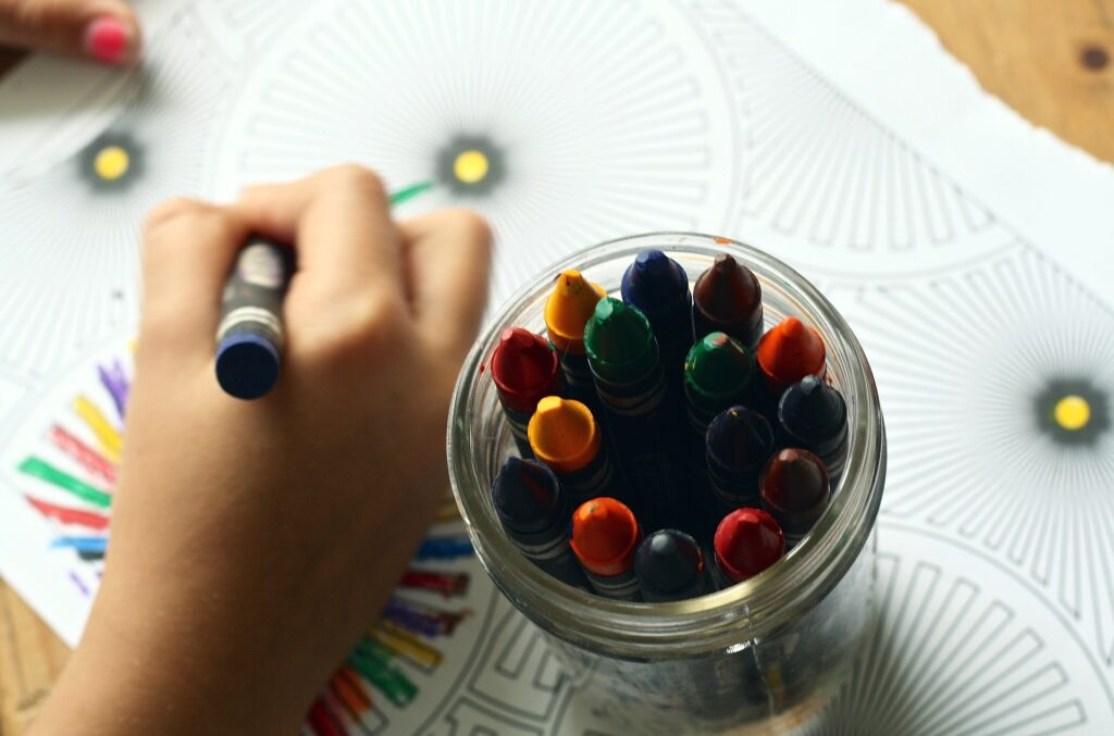 jar of wax crayons with children colouring in