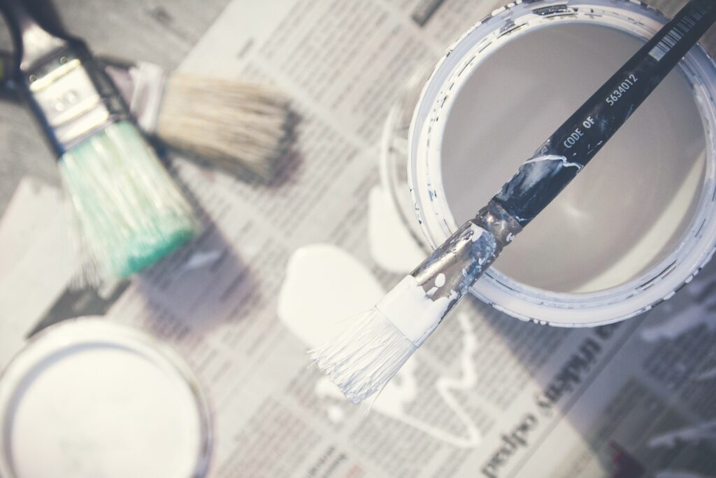 paintbrushes and paint can on newspaper