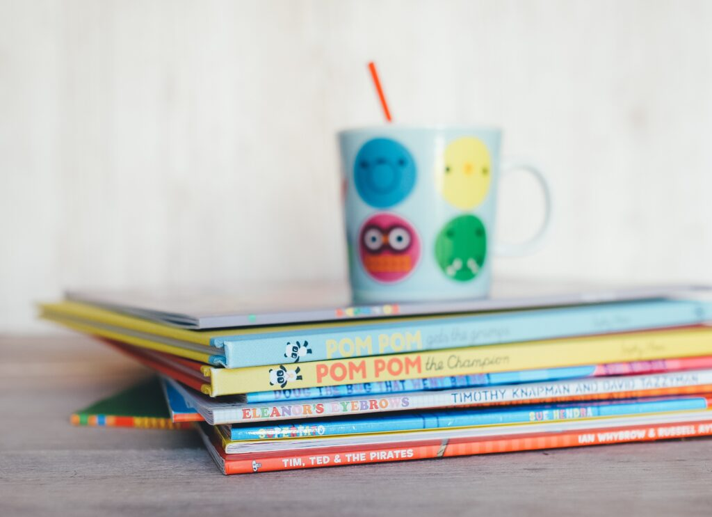 cup with straw on pile of children's books
