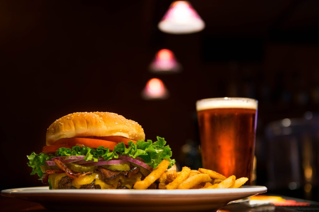 burger and chips next to pint of beer