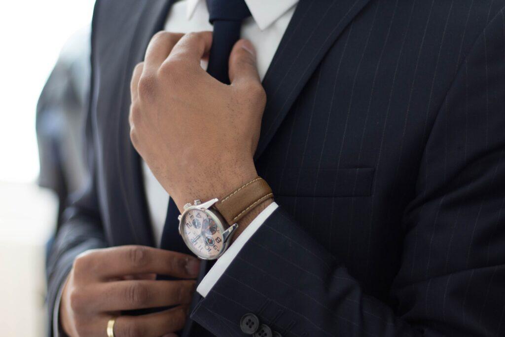 businessman straightening tie