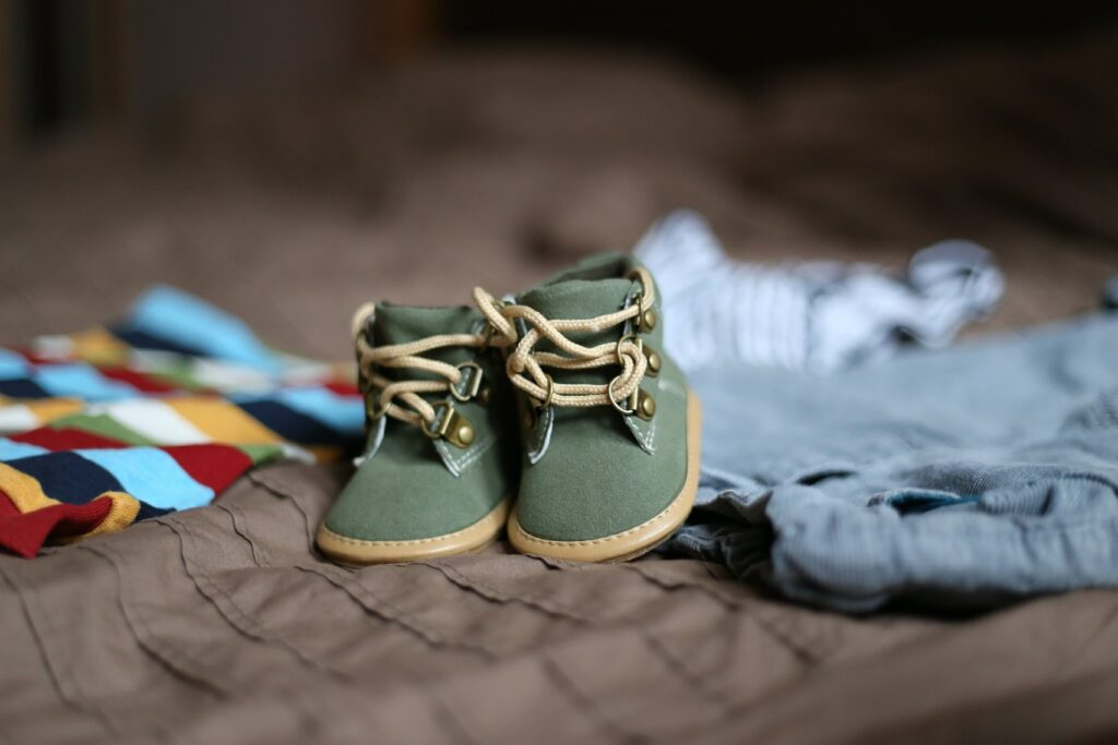 baby shoes on blanket with clothes