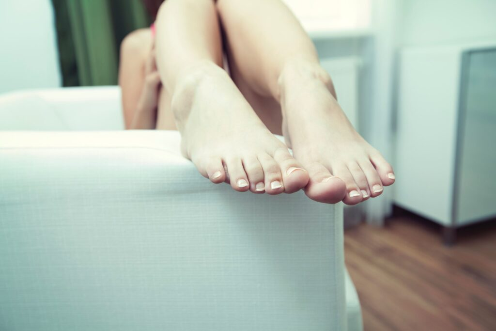 feet resting on arm of chair